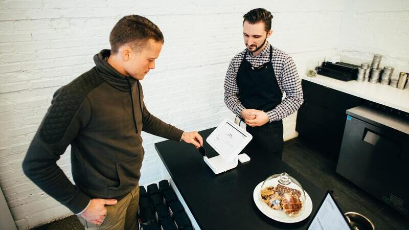 homem com a mão no bolso olhando tablet em balcão e homem de avental realizando atendimento ao cliente