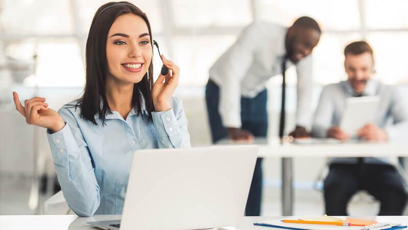em primeiro plano, mulher sentada em frente a notebook branco usando headset