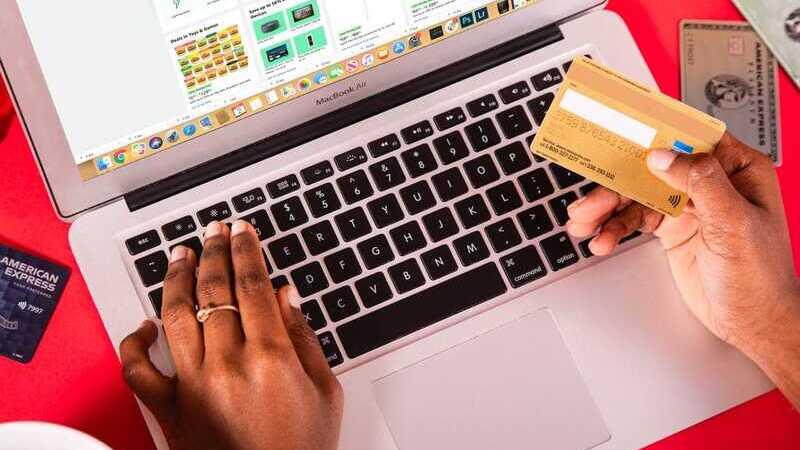 mulher segurando cartão de crédito com as mãos apoiadas sobre teclado de notebook