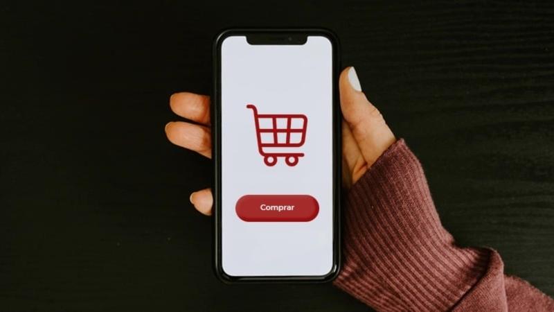 mulher segurando smartphone com figura carrinho de supermercado na tela