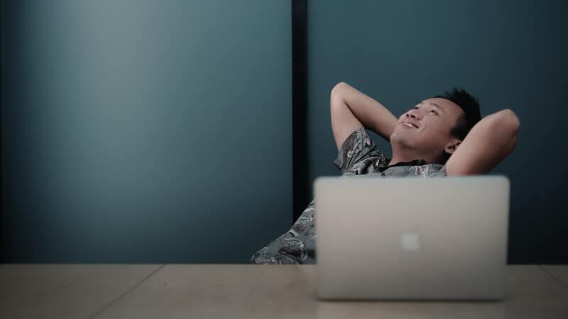 homem recostado na cadeira com os braços atrás da cabeça sentado em frente a notebook aberto