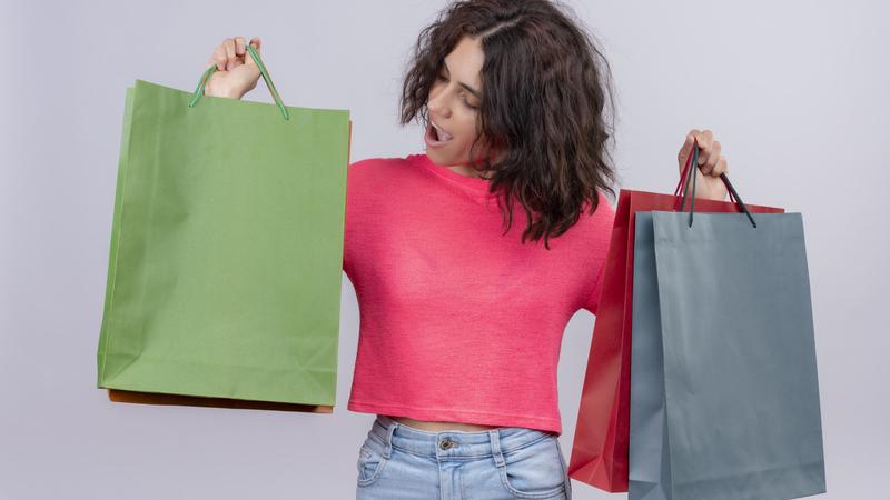 Mulher segurando várias sacolas de compras.