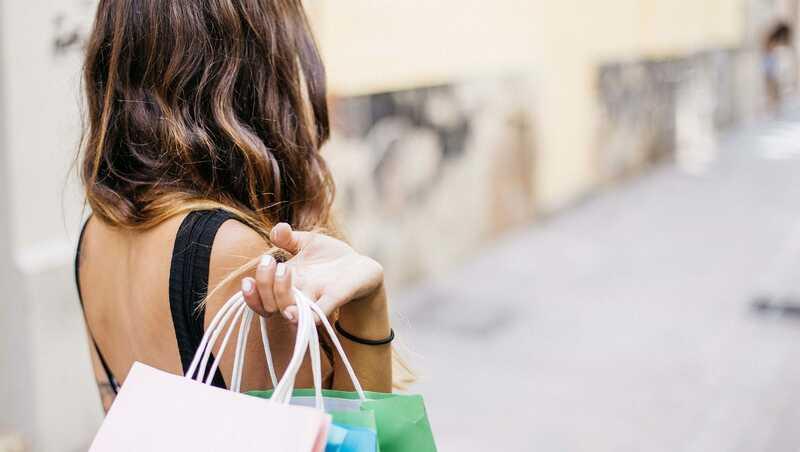mulher segurando sacolas de compras nas costas