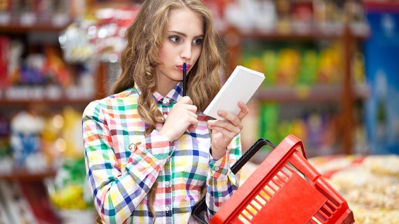 mulher no supermercado segurando bloco de anotações e caneta próxima da boca, indicando dúvida