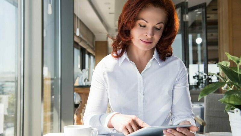 Mulher ruiva de blusa branca usando tablet em escritório.