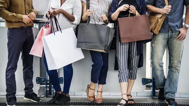 Diferentes pessoas escoradas em parede segurando sacolas de compras.
