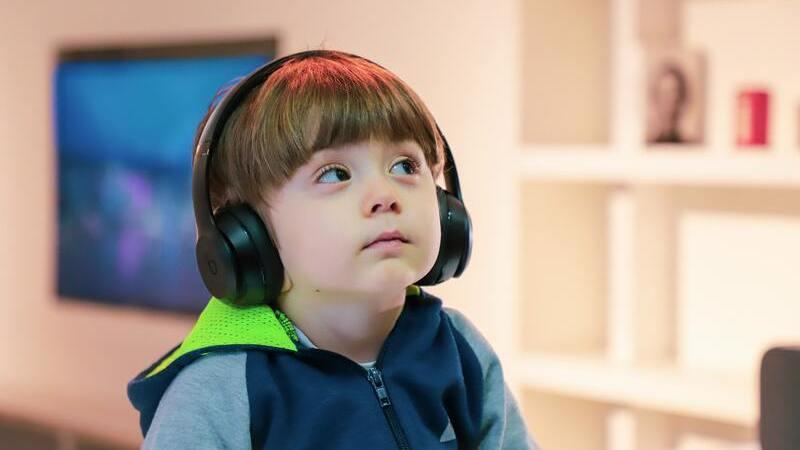 Criança usando fones de ouvido, ao fundo sala de tv.