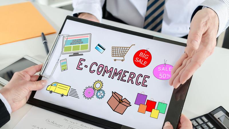 Mão segurando placa com ilustração escrito E-COMMERCE e ilustrações de elementos de compras.