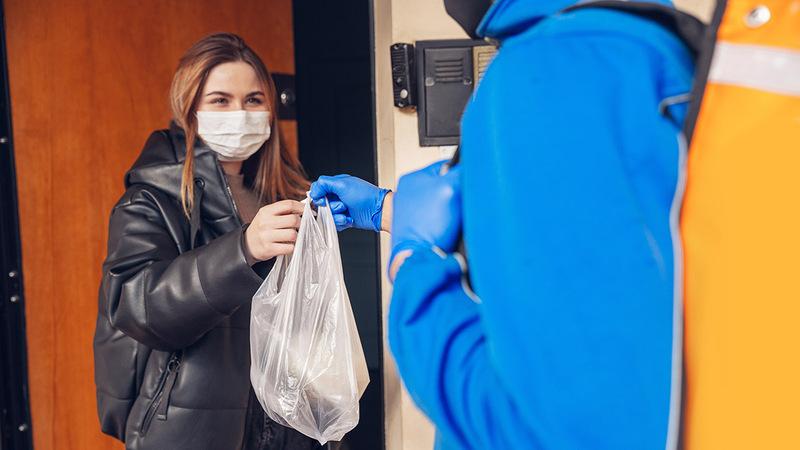 mulher usando máscara recebendo sacola de compras de entregador