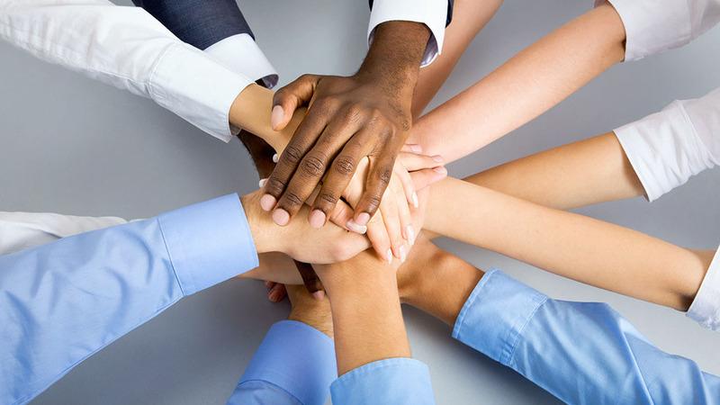 Mãos humanas unidas em círculo, umas sobre as outras, passando a ideia de união