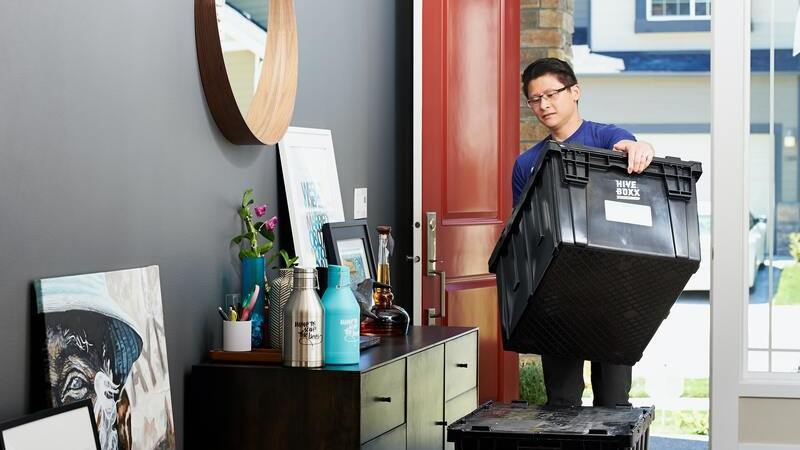 Homem carregando caixas pretas para escritório