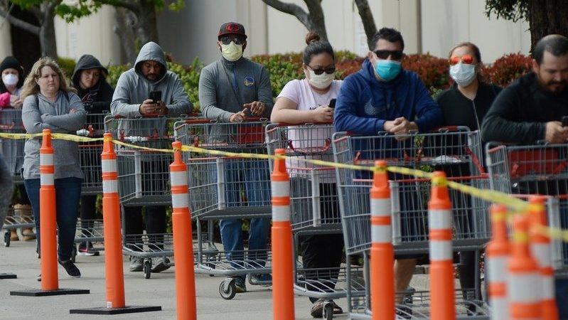 Fila de pessoas usando máscara e segurando carrinho de compras na área externa de loja.
