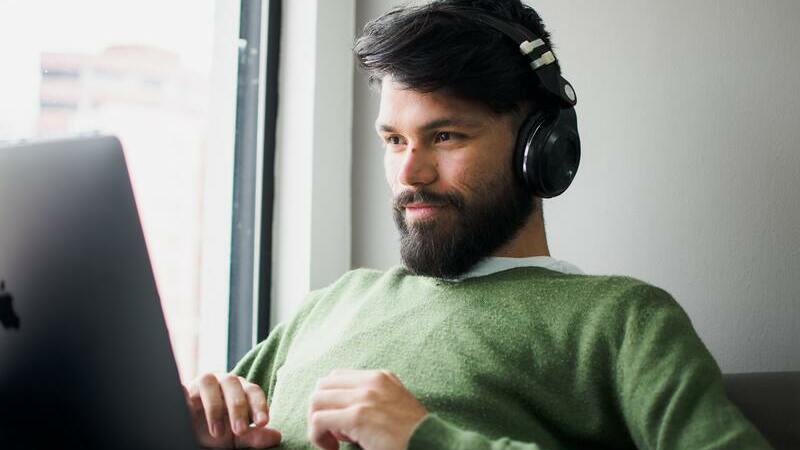 Homem de barba usando fones de ouvido com notebook apoiado sobre o colo.