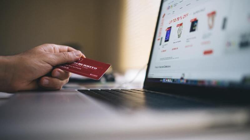 mão segurando cartão de crédito próximo de notebook ligado
