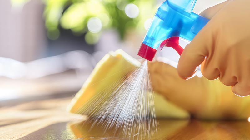 Mão com luvas de borracha segurando borrifador de produto de limpeza e pano sobre superfície.