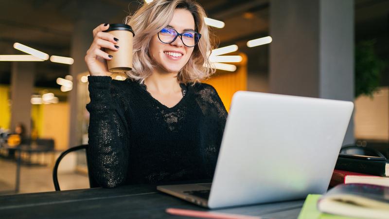 Mulher de blusa preta segurando café na mão, à frente um notebook cinza.