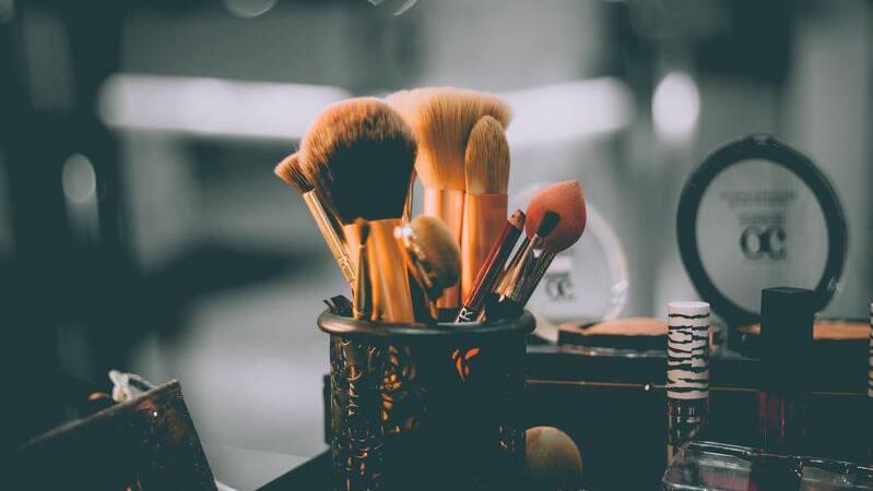Vários tipos de pincéis para maquiagem em dentro de um copo