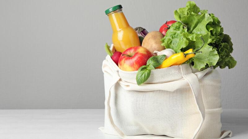 sacola de compras com frutas, verduras e uma garrafa de suco