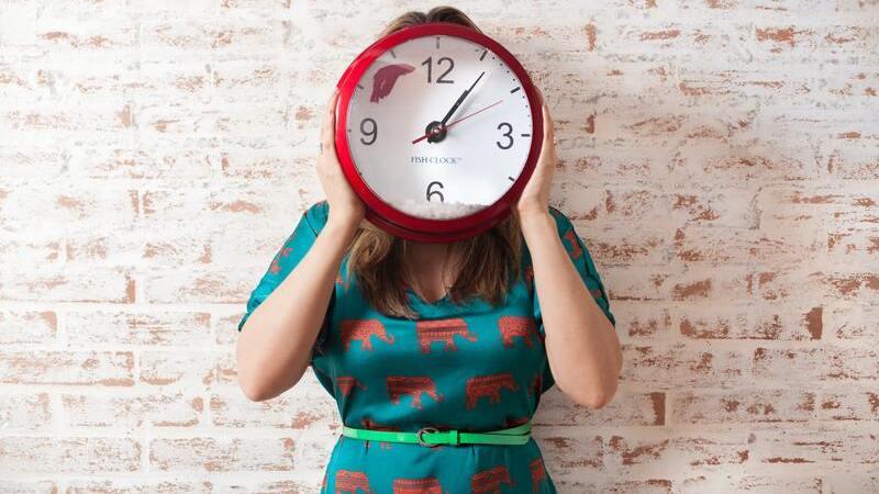 Mulher segurando relógio no rosto.