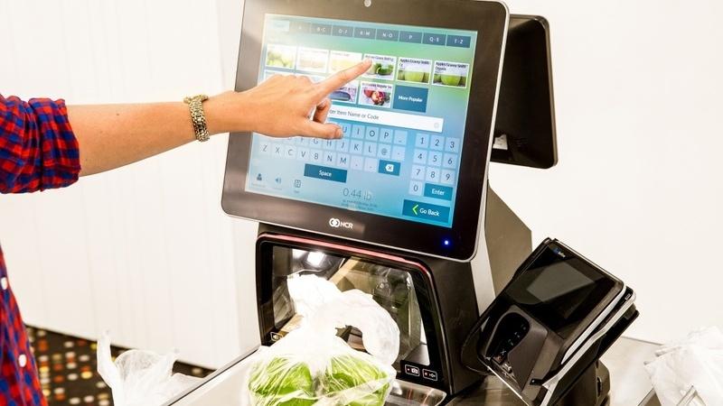 Braço de pessoa usando máquina de automação de PDV para pesar alimentos