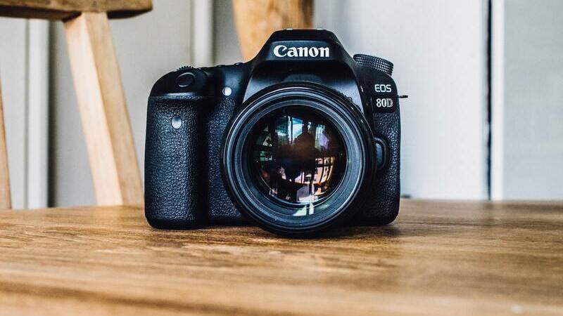 Câmera Canon preta em cima de mesa de madeira