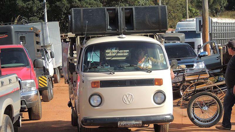 Kombi com caixas de som no teto passando por estrada de terra cheia de caminhões e caminhonetes