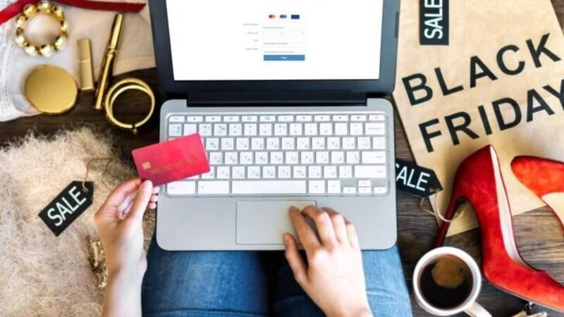 Mulher sentada com notebook no colo segurando cartão de crédito e cercada de sapatos, acessórios, cosméticos e uma sacola de papel escrito: Black Friday.