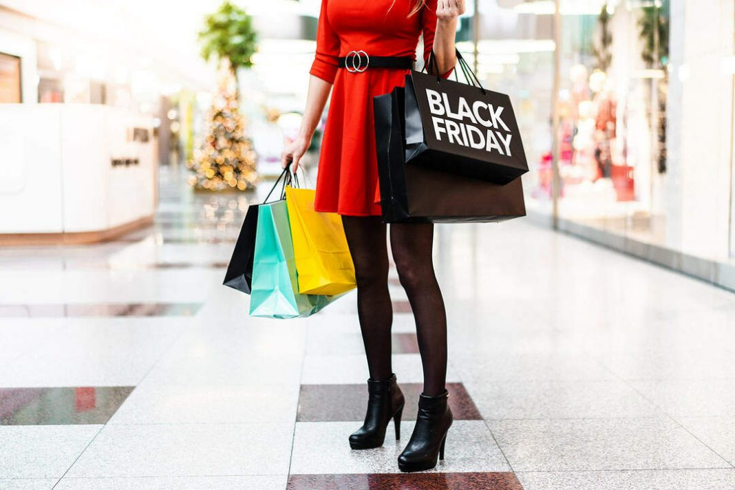 Mulher de vestido vermelho e salto alto no corredor do shopping segurando sacolas de compras