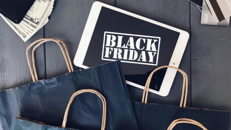 tablet com ícone da Black Friday na tela cercado de sacolas pretas e duas carteiras
