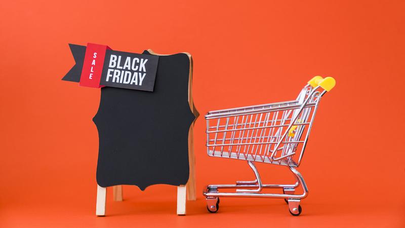 """carrinho de compras vazio perto de um letreiro com uma tag """"Black Friday"""""""