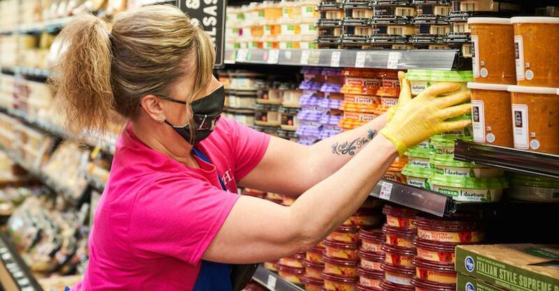 Mulher de máscara facial e luvas colocando produtos na prateleira do supermercado