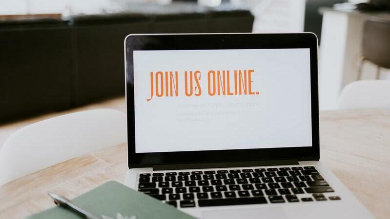 "MacBook sobre mesa de madeira com ""Join Us Online"" escrito na tela."