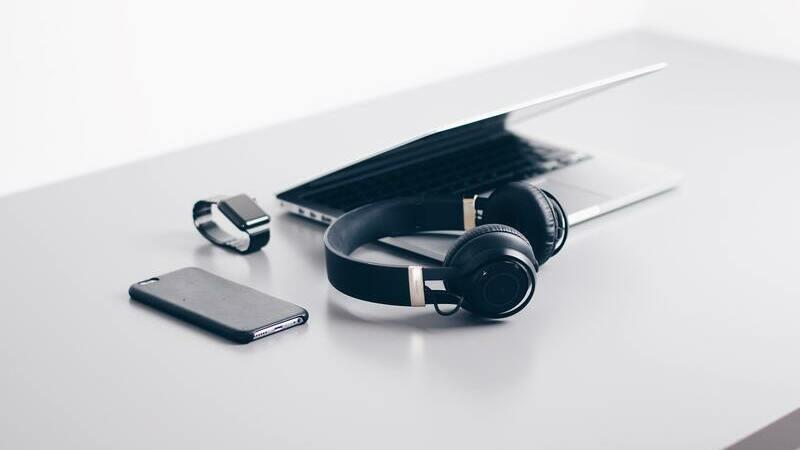 Smartphone, headphone, notebook e smartwatch sobre uma mesa