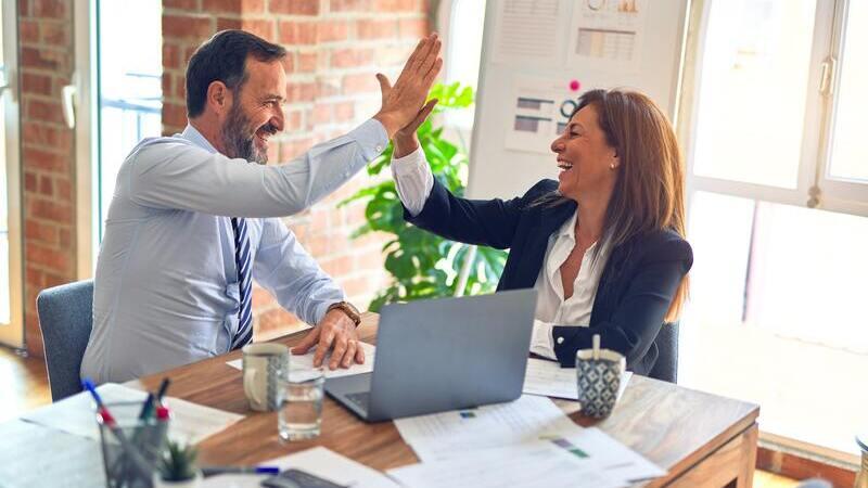homem e mulher batendo as mãos em sinal de comemoração dentro do escritório.