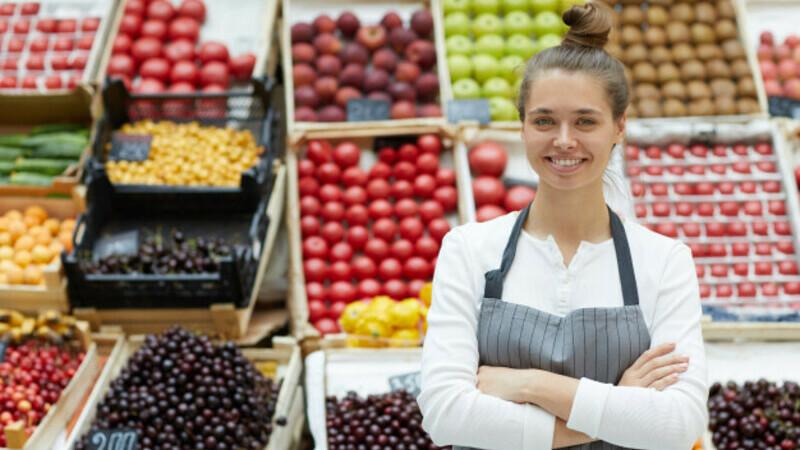 Vendedora de loja com os braços cruzados em frente a balcão de frutas.