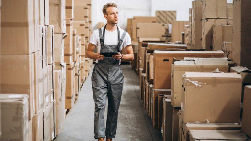 Homem andando entre caixas de papelão no estoque.