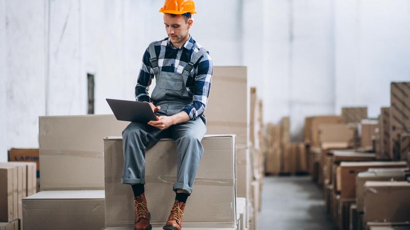 Homem com capacete de proteção usando tablet e sentado em caixas de um depósito.