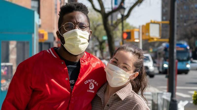Homem e mulher abraçados na rua usando máscaras de proteção