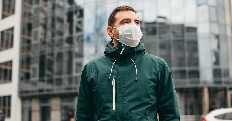 Homem de máscara em frente a prédio espelhado.