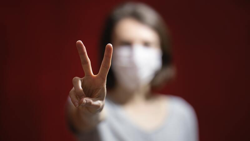 mulher de máscara fazendo sinal de vitória com a mão