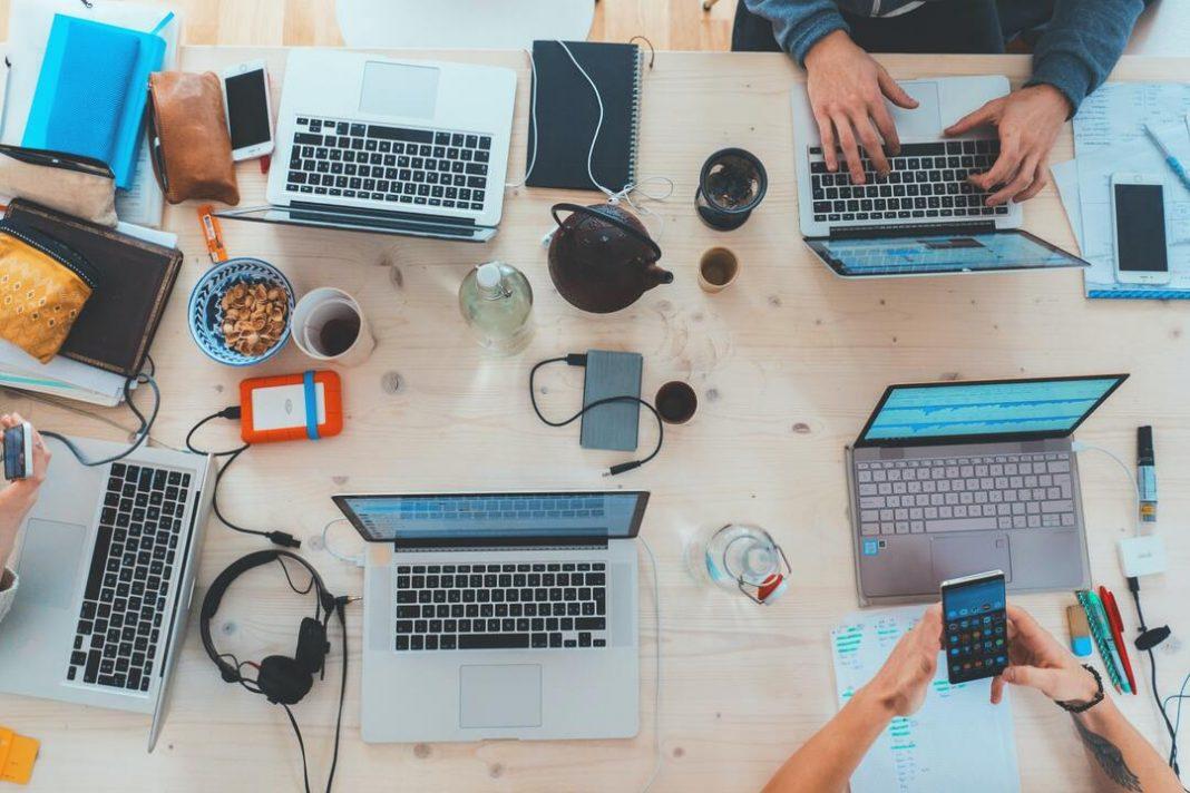 Visão de cima de uma mesa de escritório com cinco notebooks abertos e pessoas usando aparelhos eletrônicos.