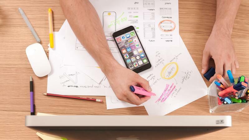 braços de pessoa sobre uma mesa com papéis, smartphone e marcadores de texto coloridos