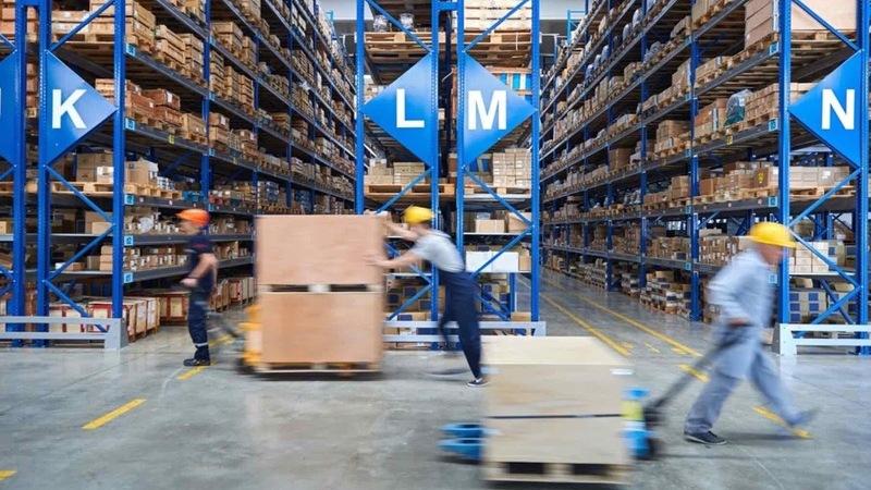 Trabalhadores puxando carrinhos com caixas e prateleiras de estoque ao fundo
