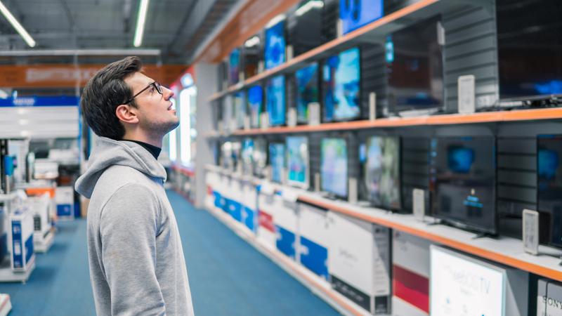 homem encarando parede com prateleiras de televisores em loja de eletrônicos
