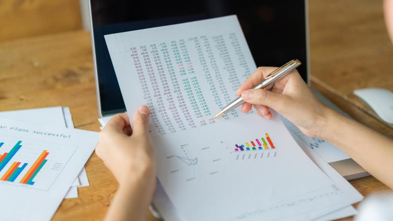 Pessoa verificando dados em folha de papel com caneta na mão.
