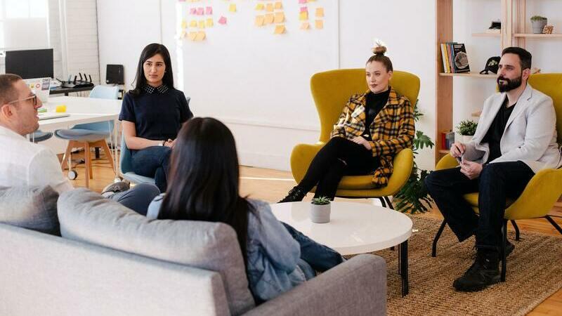 pessoas sentadas em círculo em sala de escritório durante reunião de trabalho
