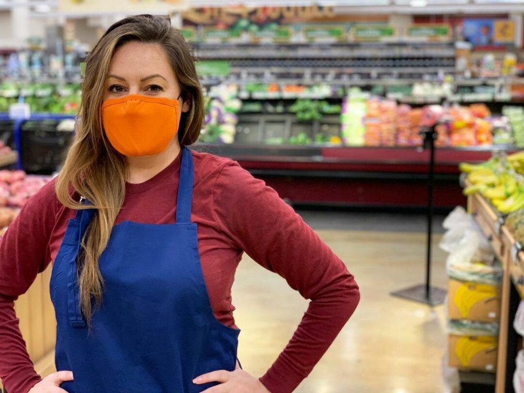 Mulher usando avental azul e máscara laranja com as mãos na cintura em setor de hortifruti do supermercado.