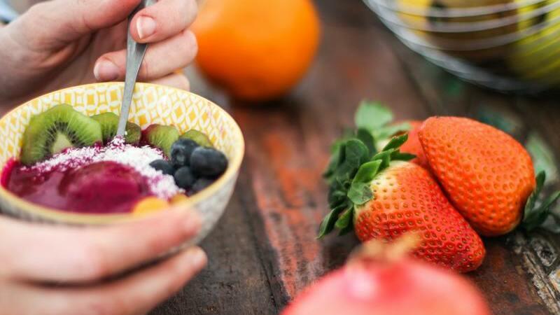 Tigela de açaó com frutas dentro e em cima da mesa. Leite em pó salpicado dentro da tigela.