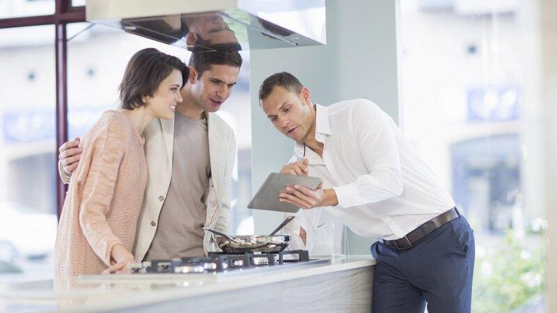 Vendedor inclinado sobre balcão de cozinha em uma loja, mostrando informações em um tablet para um homem e uma mulher.