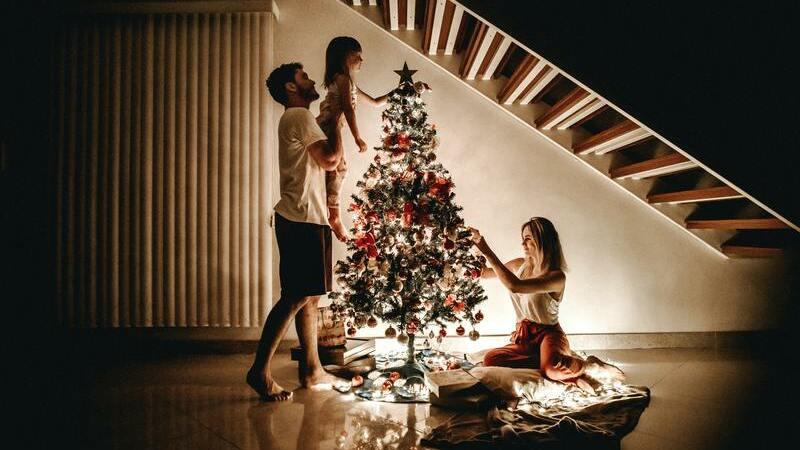 Homem, mulher e uma criança montando árvore de Natal em casa.